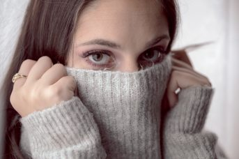 woman-covering-her-face-with-gray-knit-textile-3598464